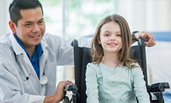 Doctor with little girl in wheelchair